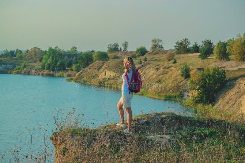 Молодая женщина с розовым рюкзаком стоит на голубом конце предпосылки карьеров мела вверх во времени захода солнца стоковые фотографии rf