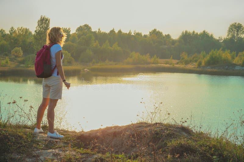 Молодая женщина с розовым рюкзаком стоит на голубом конце предпосылки карьеров мела вверх во времени захода солнца стоковая фотография