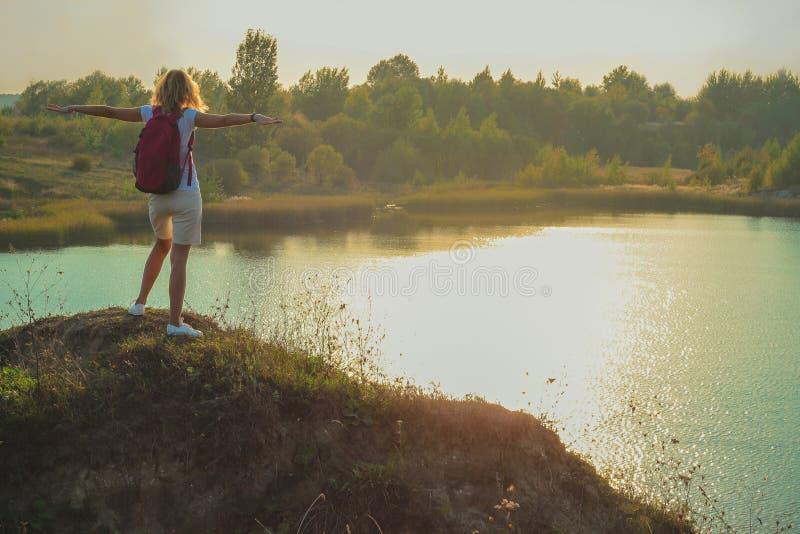 Молодая женщина с розовым рюкзаком стоит на голубом конце предпосылки карьеров мела вверх во времени захода солнца стоковые изображения rf