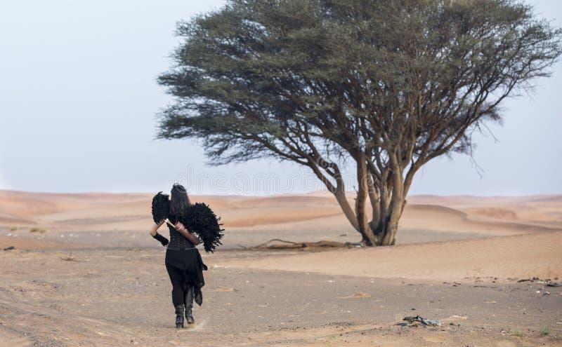 Молодая женщина с смычком и стрелка в пустыне стоковые изображения rf