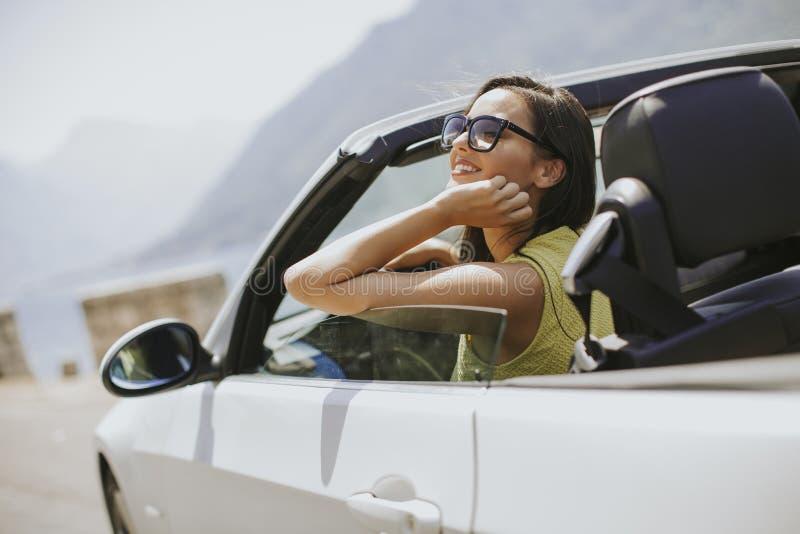 Молодая женщина с солнечными очками управляя ее обратимым верхним авт стоковые фото