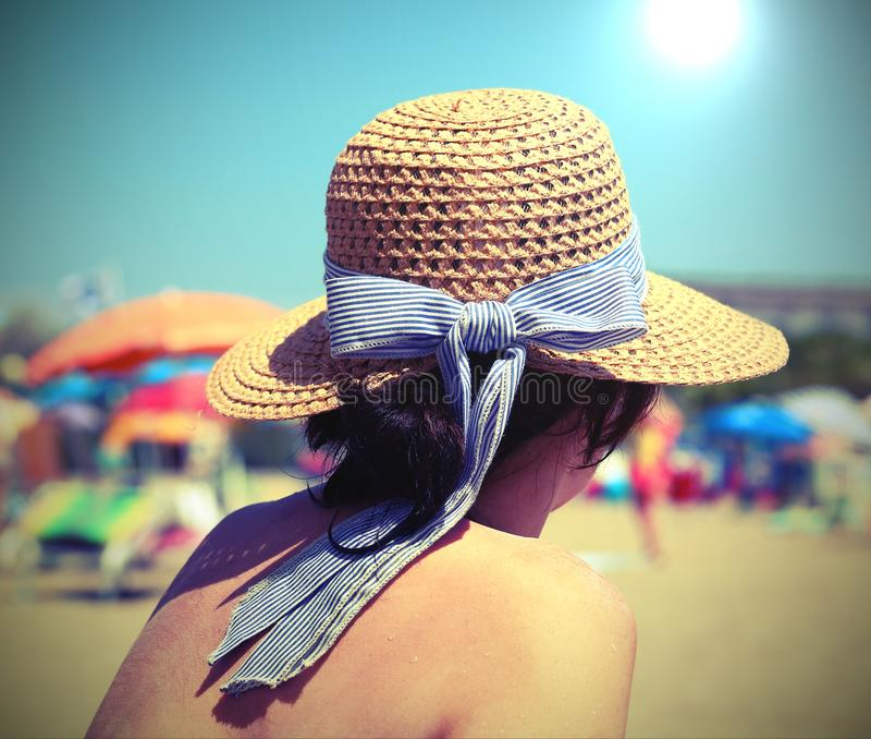 молодая женщина с соломенной шляпой на солнечном пляже с зонтиками стоковые фотографии rf