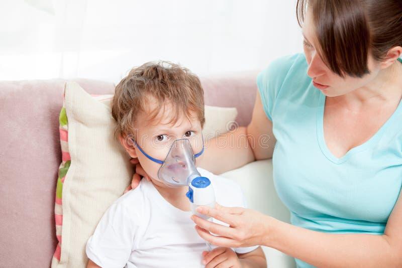 Молодая женщина с сыном делая вдыхание с nebulizer дома стоковые изображения