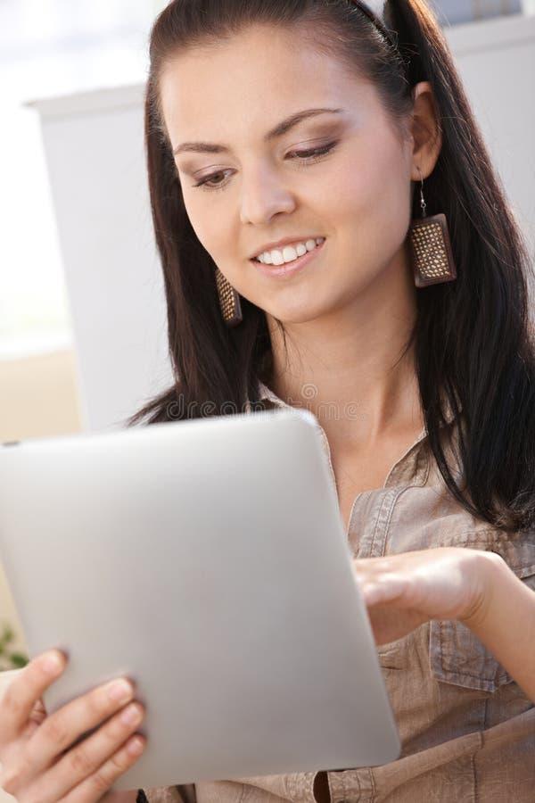 Молодая женщина с усмехаться ПК таблетки стоковые фото