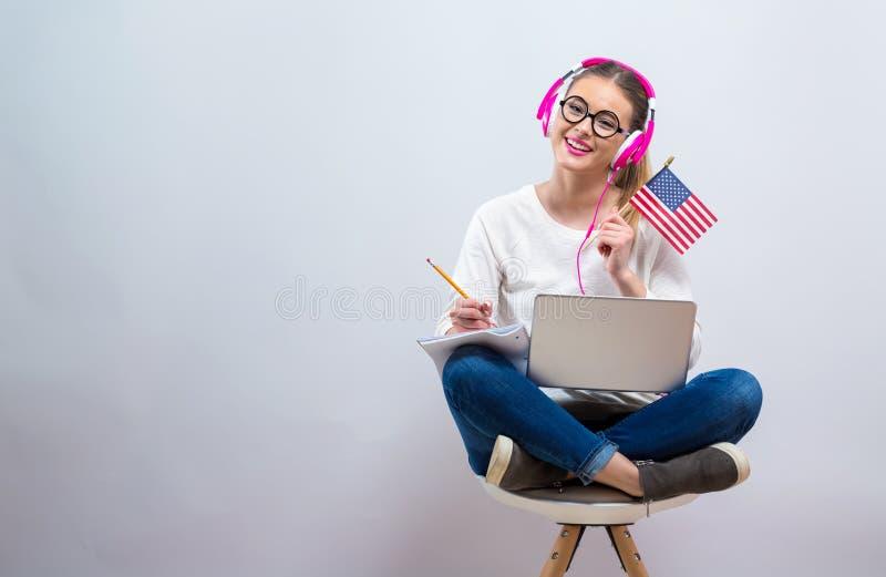Молодая женщина с флагом США используя ноутбук стоковая фотография