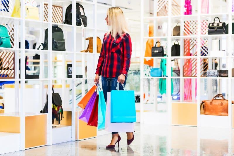 Молодая женщина с хозяйственными сумками в магазине моды стоковое изображение rf