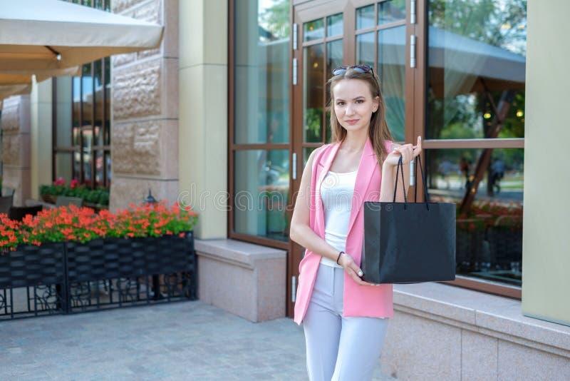 Молодая женщина с хозяйственными сумками идя на улицу города стоковая фотография