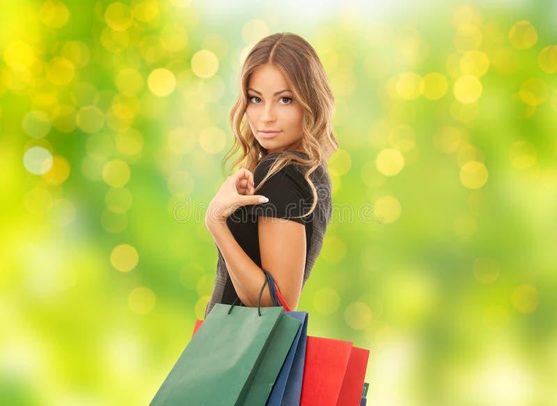 Молодая женщина с хозяйственными сумками над светами стоковые изображения
