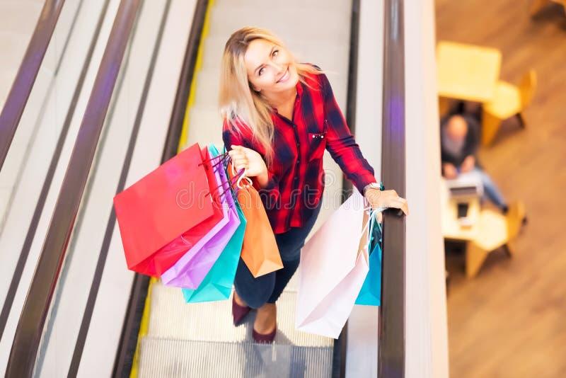 Молодая женщина с хозяйственными сумками на эскалаторе в магазине моды стоковая фотография rf
