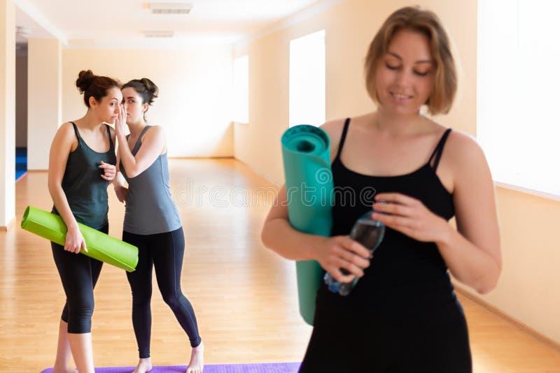 Молодая женщина с циновкой и бутылкой в ее руках На заднем плане стоит 2 женщины с циновками в их руках, шепча к каждому стоковое фото