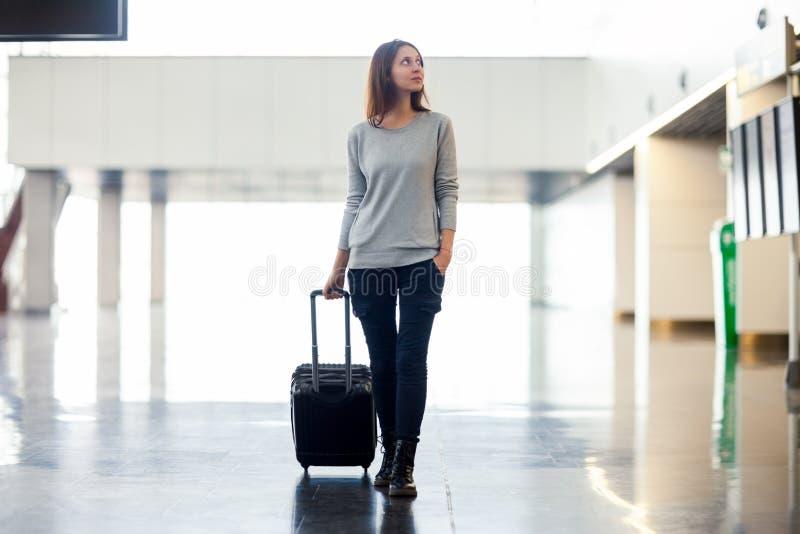 Молодая женщина с чемоданом в крупном аэропорте стоковые изображения rf