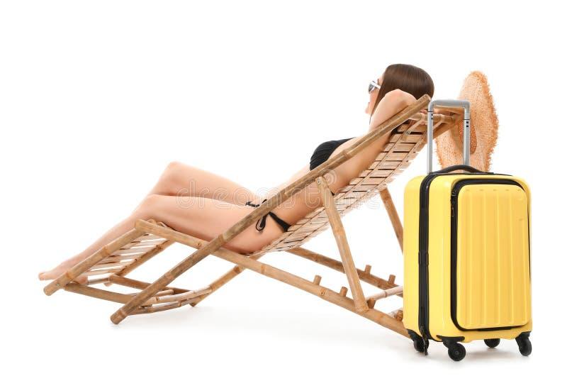 Молодая женщина с чемоданом на шезлонге против белой предпосылки стоковые изображения rf