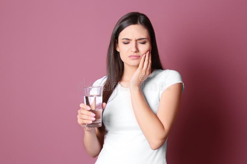 Молодая женщина с чувствительными зубами и стеклом холодной воды на предпосылке цвета стоковое фото rf