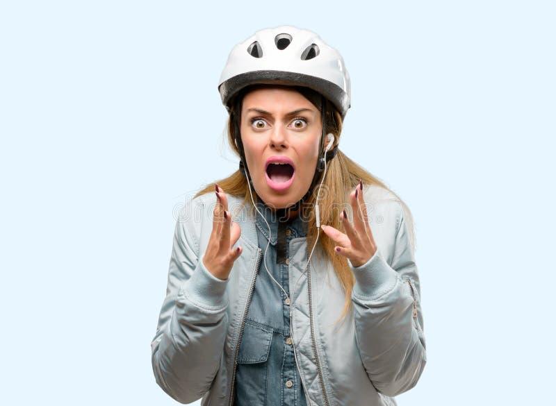 Молодая женщина с шлемом велосипеда и наушники над голубой предпосылкой стоковые изображения rf