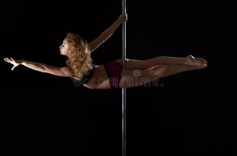 Молодая женщина танцульки полюса в бикини стоковая фотография rf