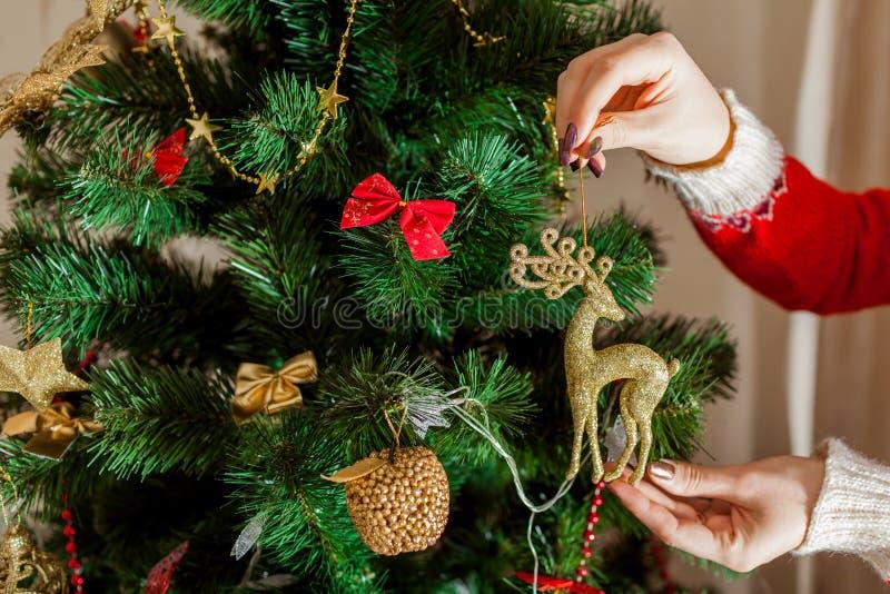 Молодая женщина украшая рождественскую елку дома, носящ свитер зимы Подготовка к Новому Году Крупный план северного оленя стоковое изображение