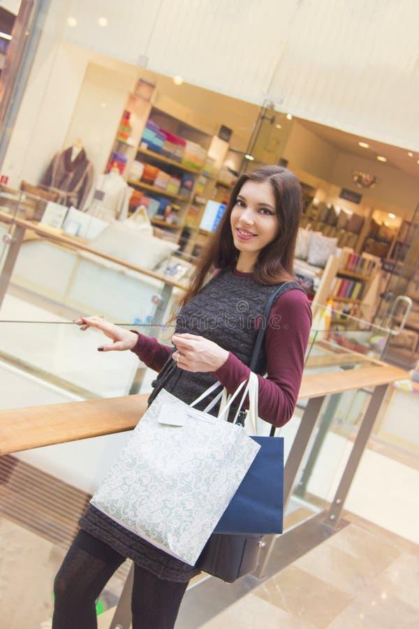 Молодая женщина усмехаясь и держа хозяйственные сумки в торговом центре стоковое изображение rf