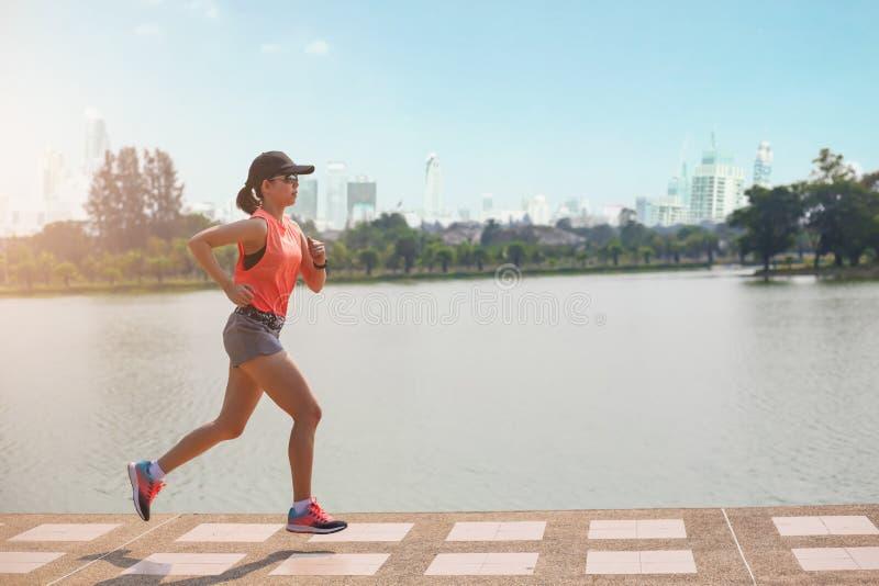 Молодая женщина фитнеса бежать в парке стоковые изображения rf