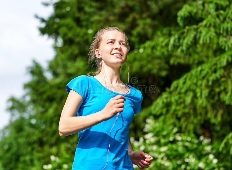 Молодая женщина фитнеса бежать на следе леса стоковая фотография rf