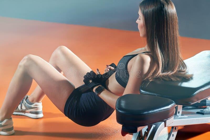Молодая женщина фитнеса выполняет тренировки в спортзале стоковая фотография
