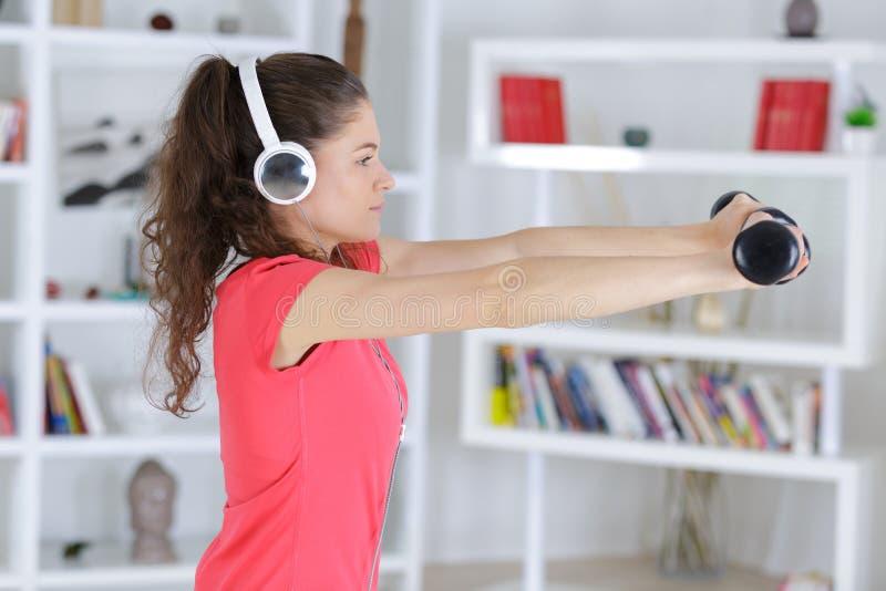 Молодая женщина фитнеса в спортзале и слушает музыка с шлемофоном стоковое фото