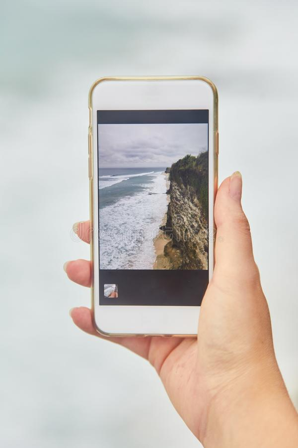 Молодая женщина фотографирует по ее телефону Девушка фотографируя ландшафт стоковая фотография rf