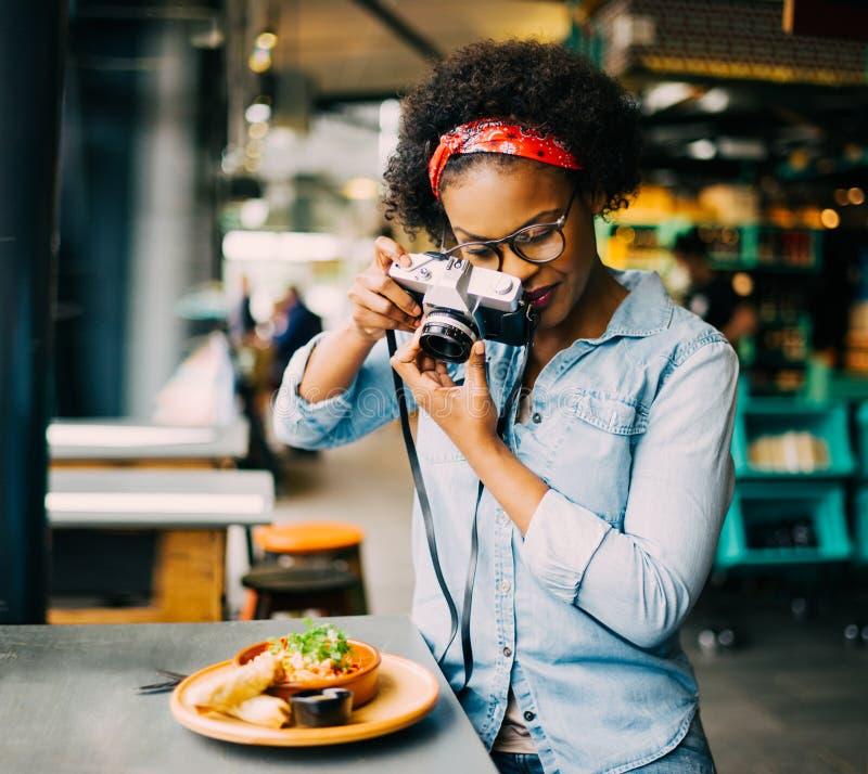 Молодая женщина фотографируя ее еду на счетчике кафа стоковая фотография rf
