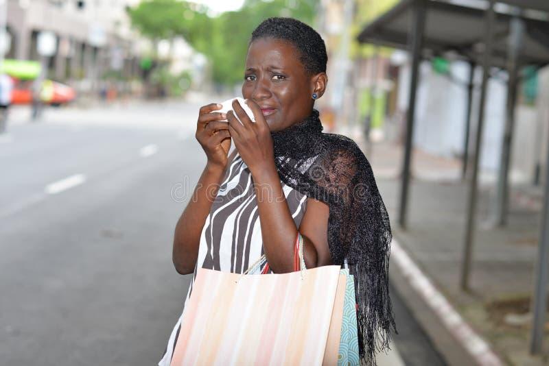 Молодая женщина хватая и кашляя на улице стоковые фото