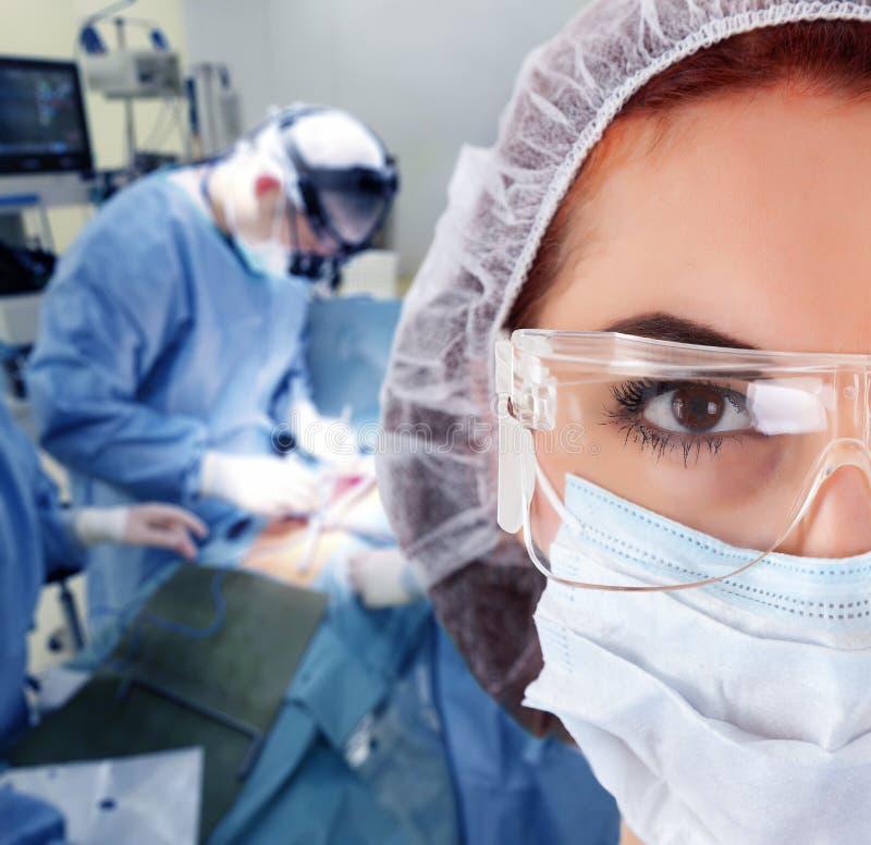 Молодая женщина-хирург из медицинской команды стоковые фотографии rf