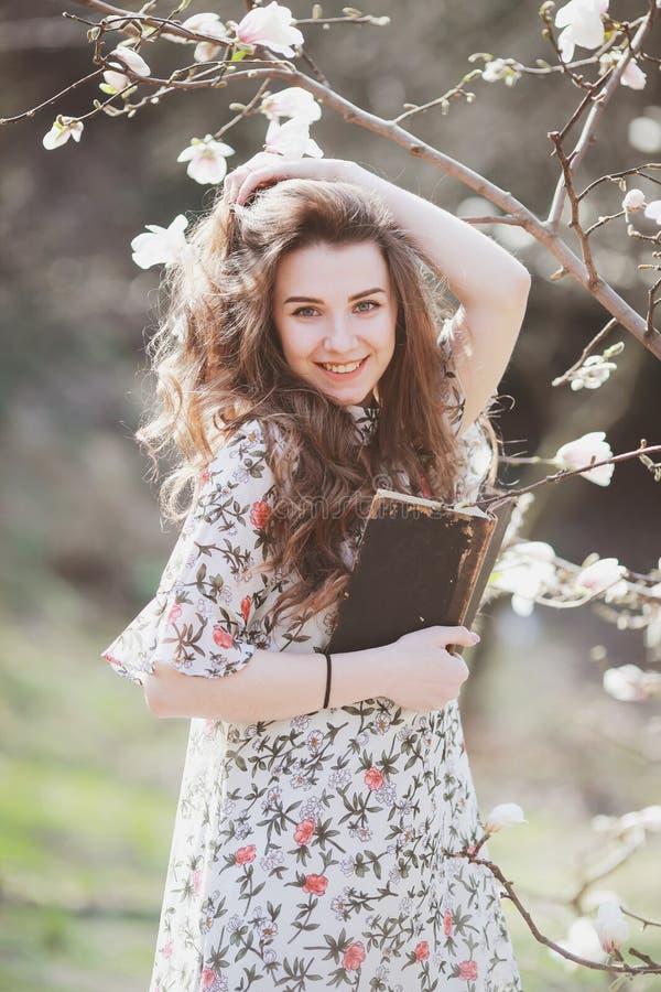 Молодая женщина читая ретро книгу в саде с зацветая деревьями стоковая фотография