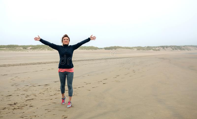 Молодая женщина чувствуя свободно на пляже стоковые изображения rf