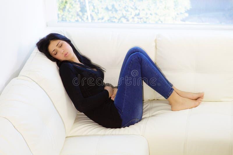 Молодая женщина чувствуя, что сильная боль менструации сидела на софе дома стоковые изображения rf