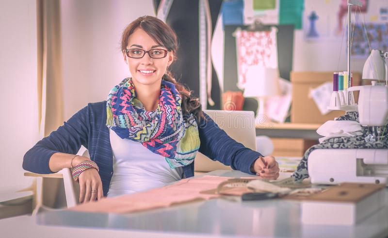 Молодая женщина шить пока сидящ на ее месте службы стоковое фото