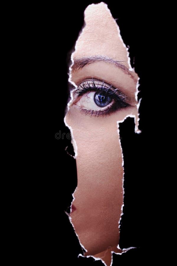 Молодая женщина шпионя через отверстие в стене стоковое фото