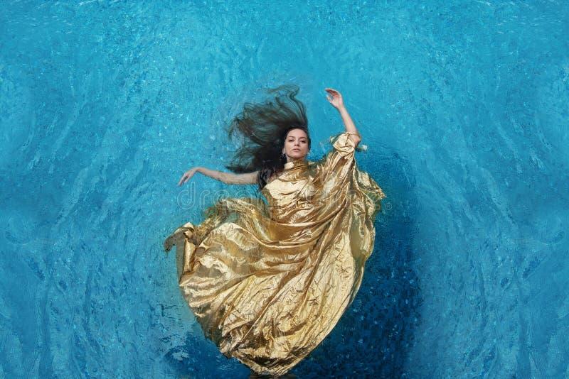 Молодая женщина Bbeautiful в платье золота, платье вечера плавая невесомо элегантный плавать в воду в бассейне стоковые фотографии rf