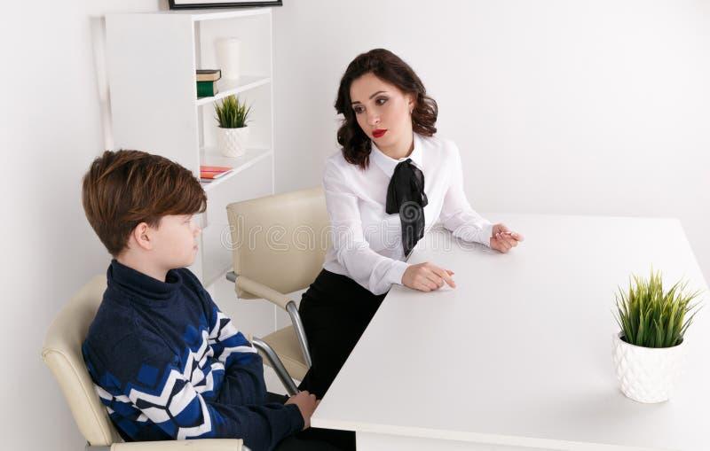 Молодая женщина brunnette говоря с мальчиком крытым белую комнату Женщина психолога с patiant Терапия психологии стоковые изображения