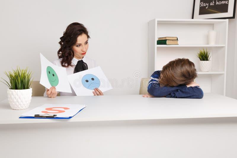 Молодая женщина brunnette говоря с мальчиком крытым белую комнату Женщина психолога с patiant Терапия психологии стоковое изображение