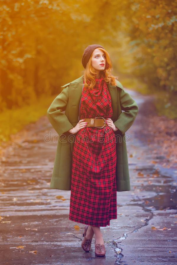 Молодая женщина redhead в красном платье с зеленым пальто на осени переплюнет стоковая фотография