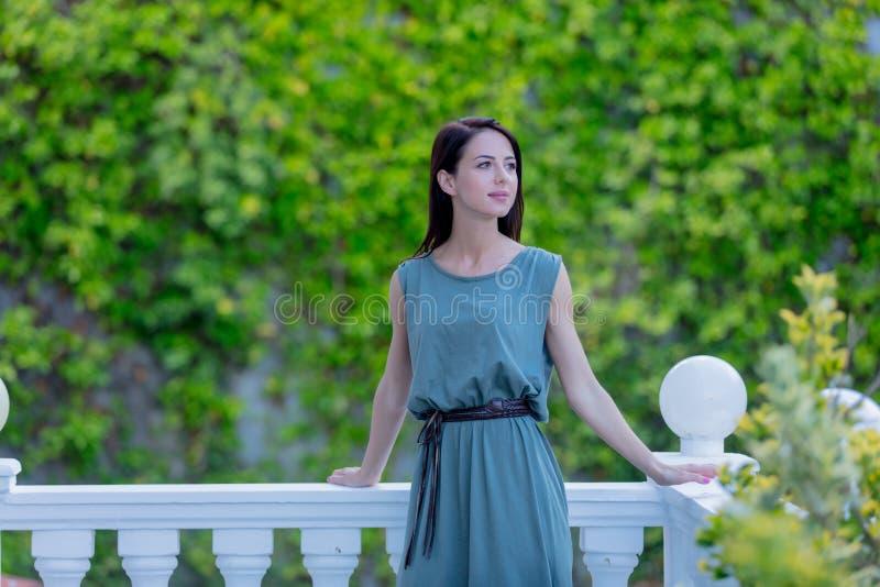 Молодая женщина redhead в платье стоя в саде, стоковое фото