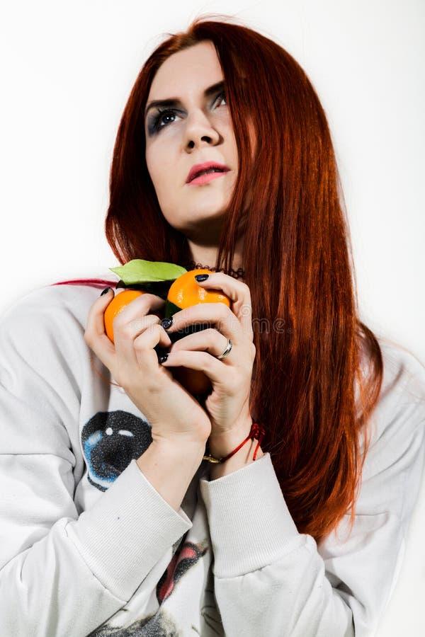 Молодая женщина redhead ест плод цитруса оранжевый имея потеху стоковое фото rf