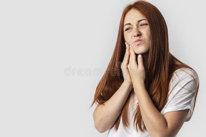 Молодая женщина redhead изолированная на серой предпосылке касаясь ее стороне и с выражением ужасного страдает от проблемы здоров стоковое изображение