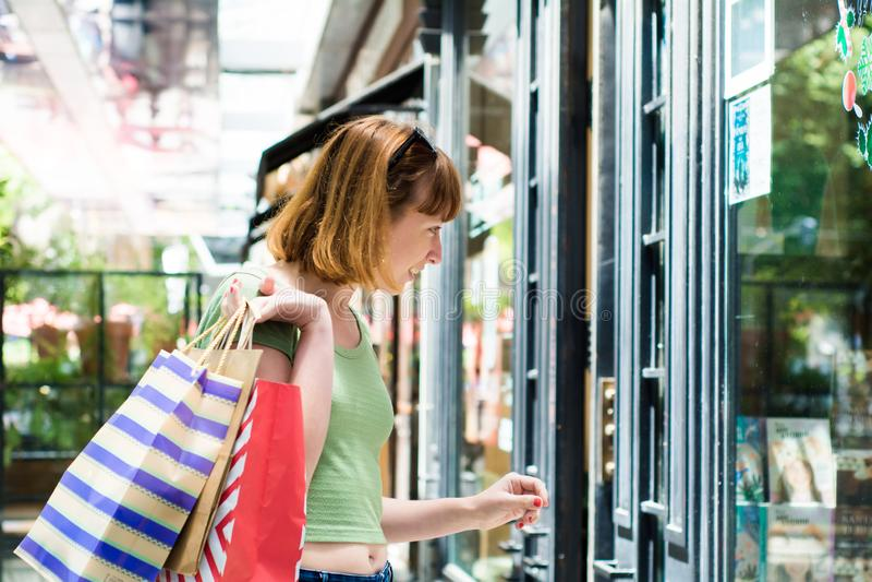 Молодая женщина redhead с хозяйственными сумками в городе стоковое изображение rf