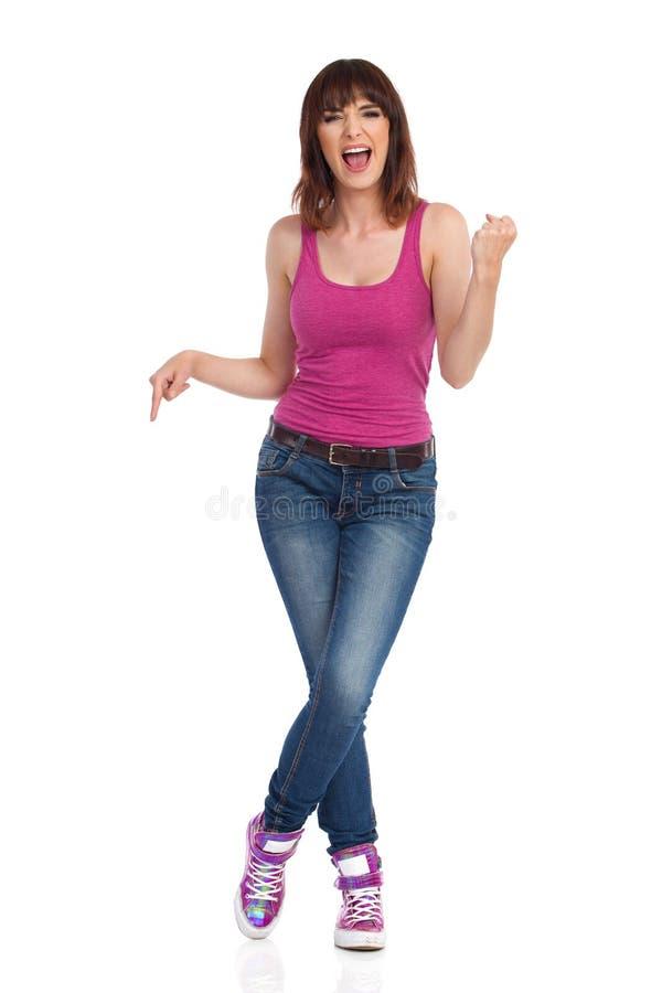 Молодая женщина Shoutng стоящ и указывающ вниз стоковые фотографии rf