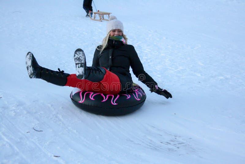 Молодая женщина Sledging вниз со сцены холма яркой и радостной зимы стоковые изображения rf