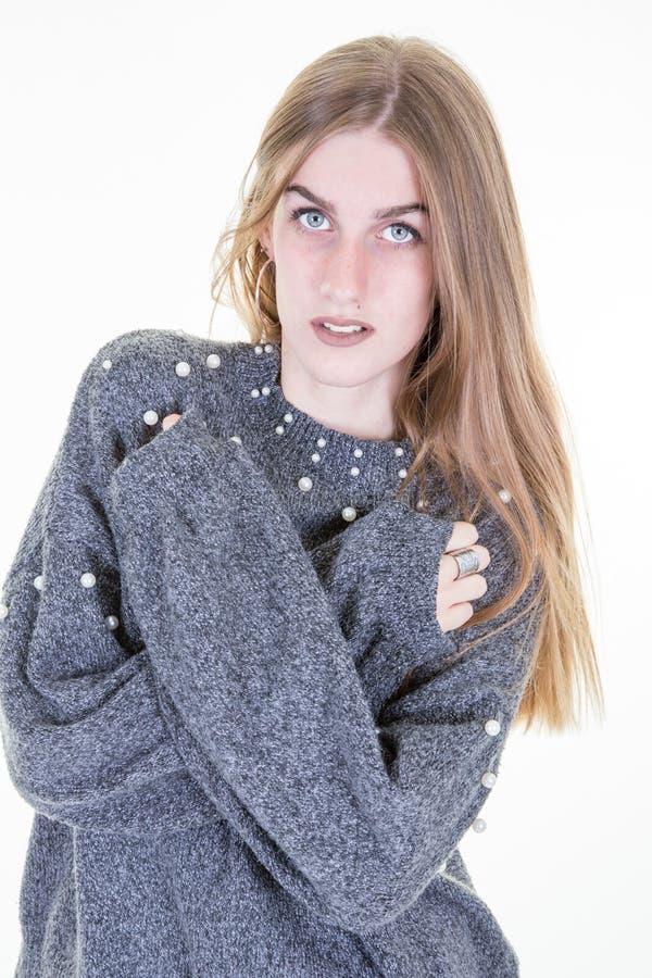 Молодая жизнерадостная женщина смотря к камере на белой предпосылке и сером свитере зимы стоковые изображения