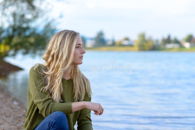 Молодая заботливая женщина сидя озером стоковое изображение rf