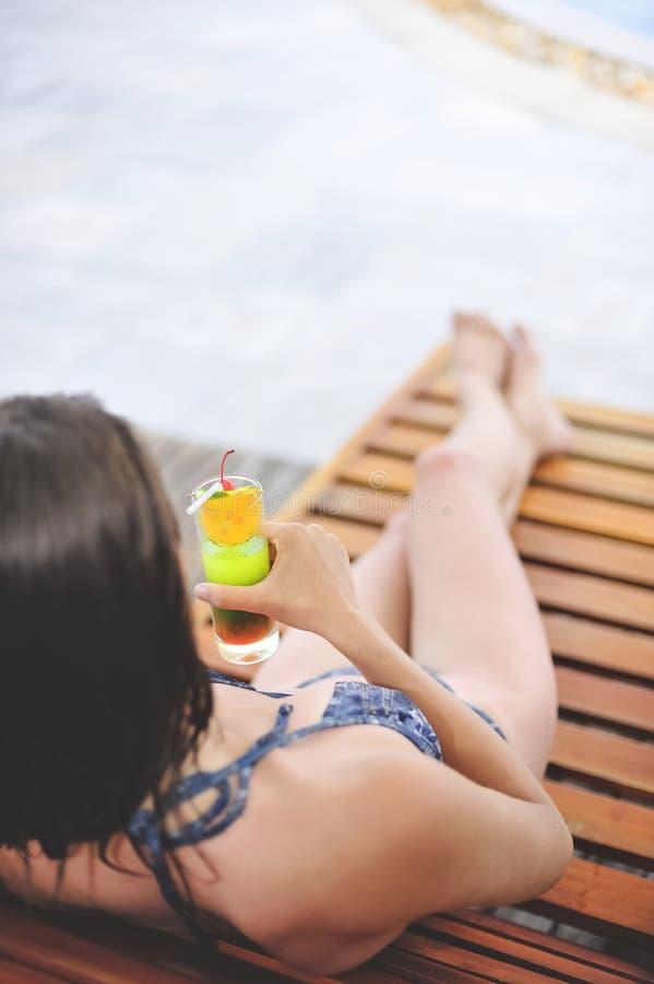 Молодая и красивая девушка на бассейне с холодным коктеилем близко к ей стоковая фотография rf