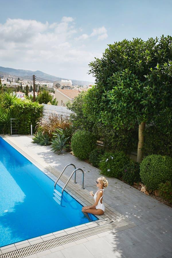 Молодая и сексуальная белокурая модельная женщина с идеальным телом в стильном белом купальнике и в солнечных очках держа стекло  стоковое изображение