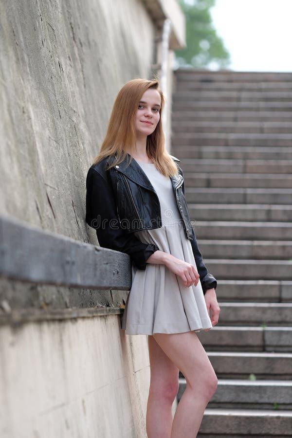 Молодая и сексуальная redheaded девушка представляя outdoors в кожаной куртке и мантии стоковые изображения rf