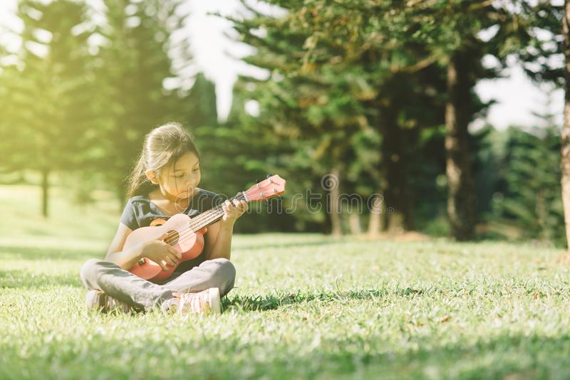 Молодая и счастливая азиатская девушка играя с гитарой ukelele на парке в солнечном утре стоковое изображение